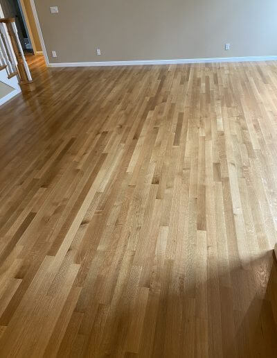Finished white oak flooring in a room with beige walls and white trim.