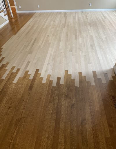 Unfinsihed white oak hardwood being laced in with existing stained hardwood as the Barnum Floors team refinishes the hardwood in the room.