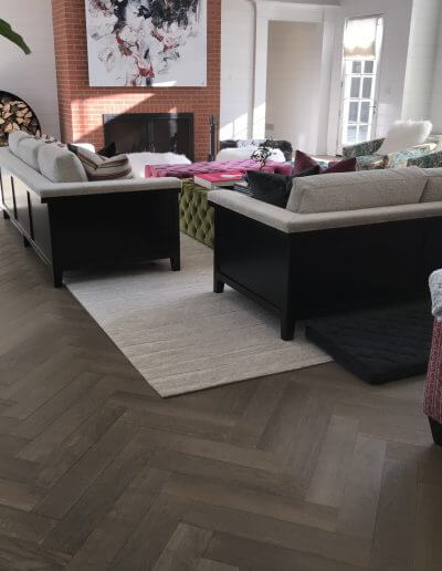 A living room featuring taupe-colored pre-finished hardwood flooring.