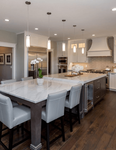 A light-colored kitchen with dark hickory hardwood flooring by Barnum Floors.