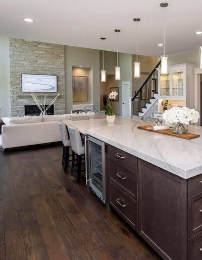 An open-concept kitchen and living room area that showcases dark hickory hardwood flooring.