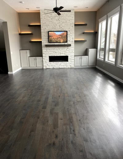 A living room with hickory hardwood flooring, paired with beige walls, white trim, and a beige fireplace.