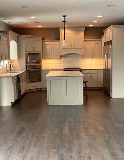 Taupe-colored hickory hardwood flooring in a kitchen with off-white cabinets and backsplash and stainless steel appliances.