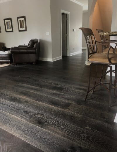 Dark-colored pre-finished hardwood flooring featured in a dining room space with grey walls and white trim.