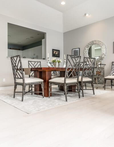 Bleached maple hardwood flooring featured in a dining room with grey walls, a wooden table, and neutral-colored furniture.