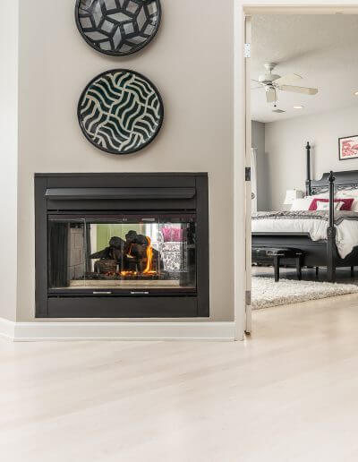 Bleach stained maple hardwood flooring featured in a living room area with a fireplace and light grey walls.