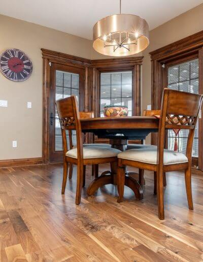A dining room featuring warm brown-colored hardwood flooring, large windows, and dark wood trim.