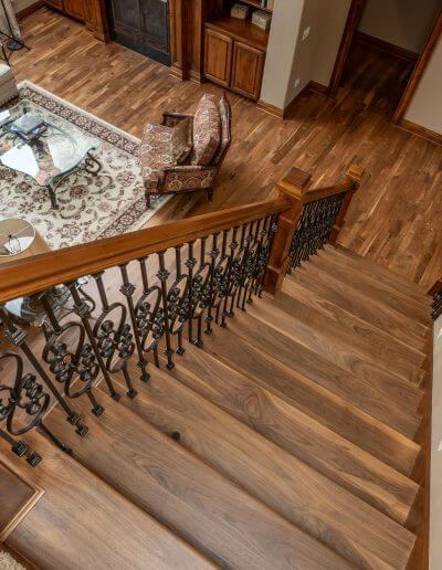 Stairs featuring natural-colored hardwood flooring, leading down to more hardwood in a living room.