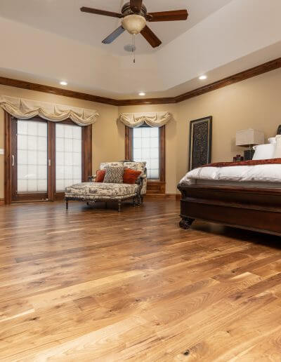 A beautiful master bedroom featuring golden hardwood floors, golden beige walls, dark wood trim, and a white ceiling.