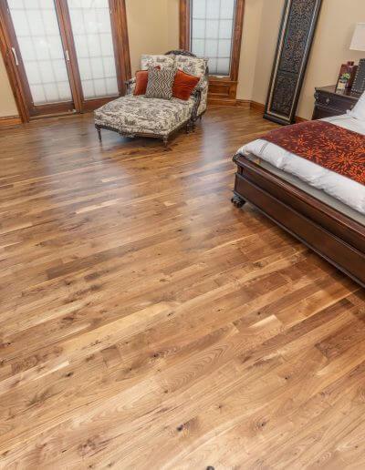 A beautiful master bedroom featuring warm hardwood flooring, beige walls, dark wood trim, and bedroom furniture.