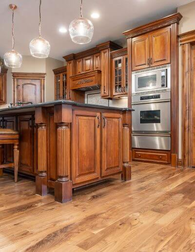 A kitchen featuring beautiful hardwood floors from Barnum Floors, along with rich wooden cabinetry, beige walls, and stainless steel appliances.