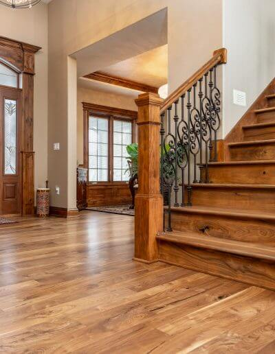 Beautiful hardwood featured in flooring and a staircase in a home with beige walls.