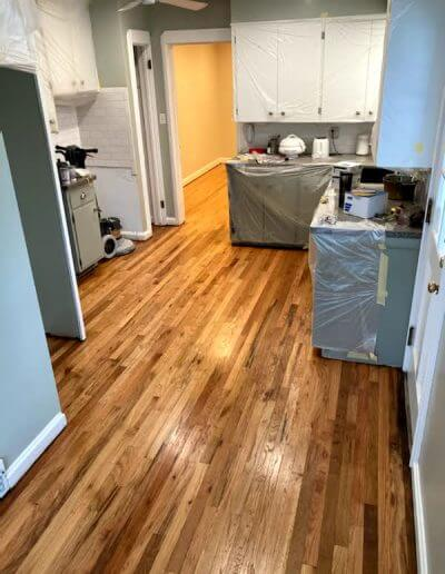 Refinished red oak hardwood flooring in a kitchen with plastic covering the counters and cabinets.