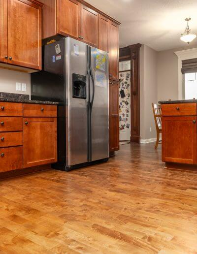 Maple hardwood flooring featured in a kitchen with wooden cabinets, beige walls, and stainless steel appliances.