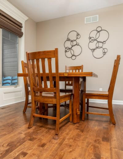 A dining room area featuring rich maple hardwood flooring with a wooden dining table set.