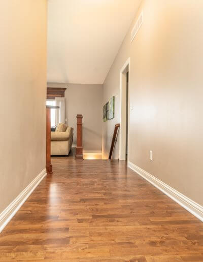 Maple hardwood flooring featured in a hallway with beige walls and white trim.