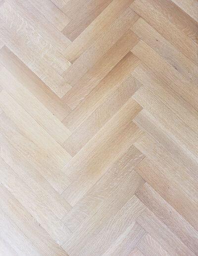 A close-up picture of white oak hardwood in a herringbone pattern.