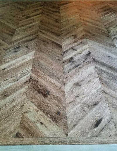 A close-up picture of white oak hard in a chevron pattern that's been wire brushed.