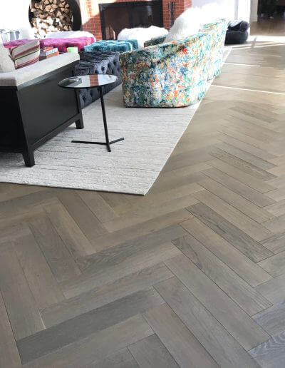 Taupe-colored pre-finished engineered hardwood in a herringbone pattern.