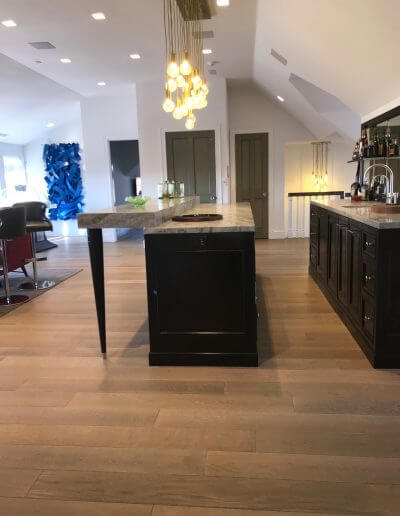 Neutral brown-colored pre-finished hardwood flooring in a kitchen and dining room space.